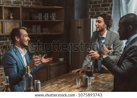 cheerful young multiethnic men talking and drinking whiskey together