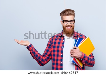 Cheerful young nerdy red bearded student is standing with books on pure background in glasses and casual bright outfit, holding something - copyspace