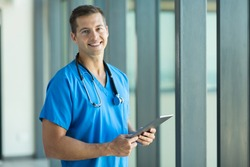 cheerful young nurse with tablet pc in office