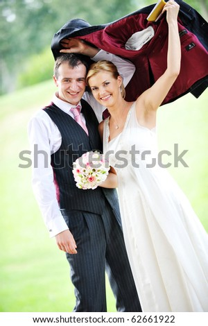 cheerful young pair in  wedding day hides from  rain