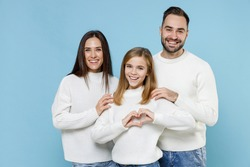 Cheerful young parents mom dad with child kid daughter teen girl in sweaters showing shape heart with hands heart-shape sign isolated on blue background studio portrait. Family day parenthood concept