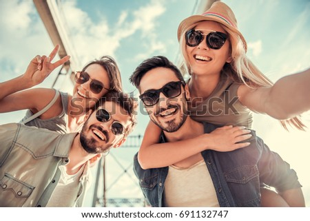 Cheerful young people are looking at camera and smiling while walking in the city, girls sitting pickaback
