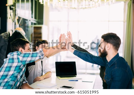 Cheerful young people giving each other high-five with smile while sitting at the office table on business meeting #615051995
