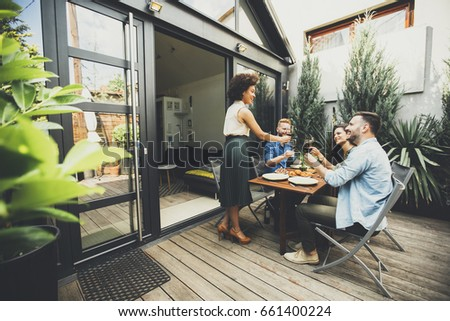 Cheerful young people have lunch in the courtyard and have a fun