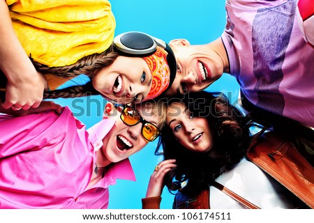 Cheerful young people laughing over blue sky.