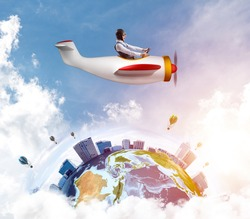 Cheerful young pilot sitting in cabin of small airplane. Funny man in aviator hat with goggles driving propeller plane. Traveling around the world by airplane. Earth globe among cloudy skyscapes.