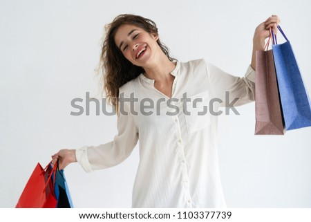 73b15b3fc47d5 Cheerful young pretty woman raising shopping bags, dancing and looking at  camera. Consumerism concept