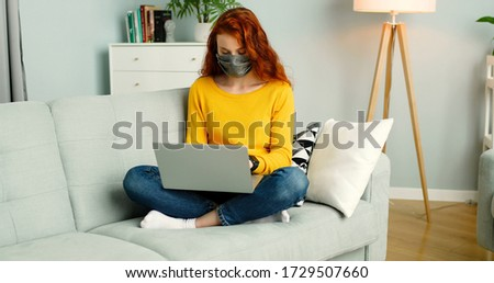 Cheerful young redhead girl in mask sitting on sofa in living room at home and using silver laptop.