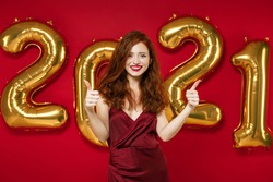 Cheerful young redhead woman in elegant dress showing thumbs up isolated on red color background, golden numbers air balloons studio portrait. Happy New Year 2021 celebration holiday party concept