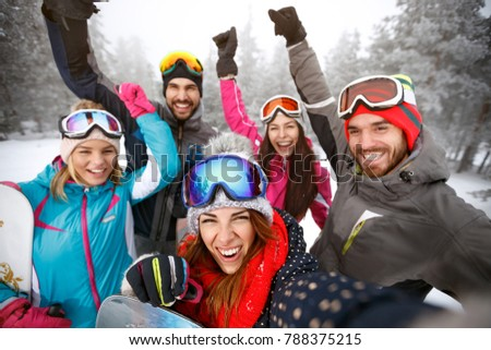 Cheerful young skiers on skiing together on snow