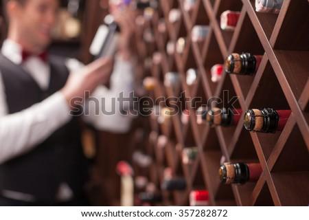Cheerful young sommelier is choosing wine in cellar. He is smiling. Focus on bottles in shelf
