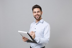 Cheerful young unshaven business man in light shirt posing isolated on grey background. Achievement career wealth business concept. Mock up copy space. Hold clipboard with papers document write notes