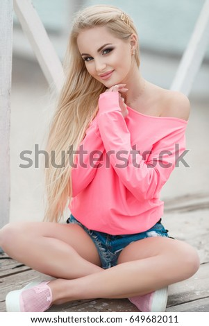 6eafae4d626e12 Cheerful young woman at beach smiling outdoor portrait. Blonde beautiful  hipster girl wear shorts and