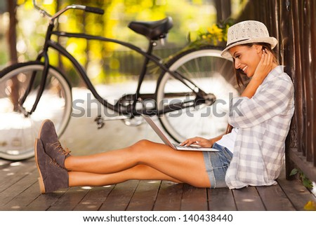 cheerful young woman browsing internet on her laptop outdoors at the park