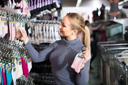 Cheerful young woman choosing pair of socks in clothes shop