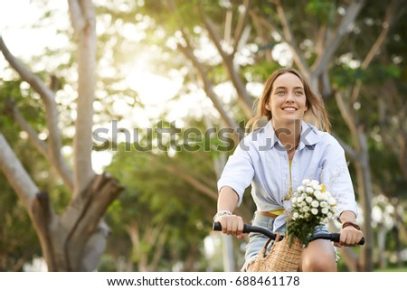 Cheerful young woman cycling in the park with flowers in basket #688461178