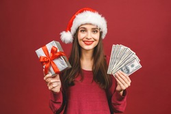 Cheerful young woman dressed in red sweater wearing christmas hat standing isolated over red wall background holding money and surprise gift box.