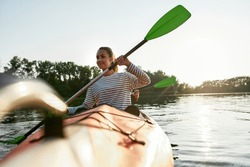 Cheerful young woman enjoying kayaking with her friend in a lake on a summer day. Kayaking, travel, leisure concept