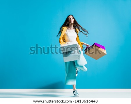 Cheerful young woman enjoying shopping: she is walking and swinging her shopping bags, sales and fashion concept
