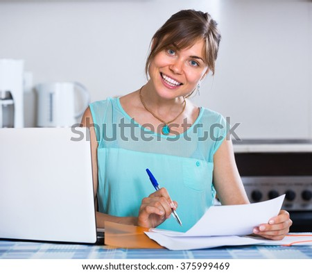 Cheerful young woman filling banking documents and smiling at the kitchen