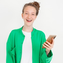 Cheerful young woman girl in green shirt posing isolated on gray wall background studio portait. People lifestyle concept. Happy Teen Using mobile phone typing sms message Winer