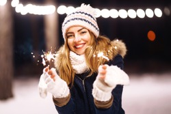 Cheerful young woman holding a sparkler in hand  in the winter forest. Happy cute girl in knitted hat posing with sparkler. New year's eve with bengal light. Woman happiness and playing firework.