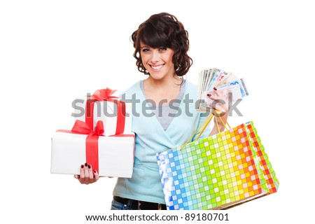 cheerful young woman holding paper money and gifts. isolated on white background