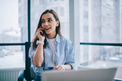Cheerful young woman in casual wear having telephone conversation sitting at working place near laptop in office, smiling female freelancer calling to colleague for share good news about business