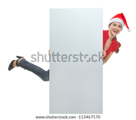 Cheerful young woman in Christmas hat holding blank billboard