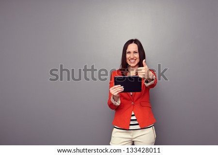 cheerful young woman in red jacket holding tablet computer and showing thumbs up over grey background - stock photo