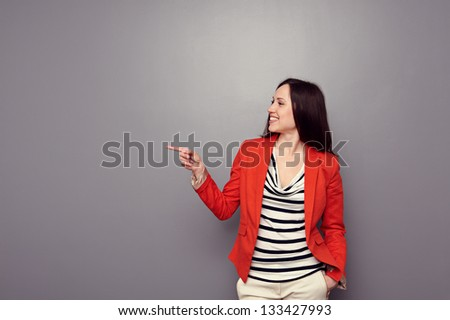 cheerful young woman in red jacket pointing at empty copyspace over grey background