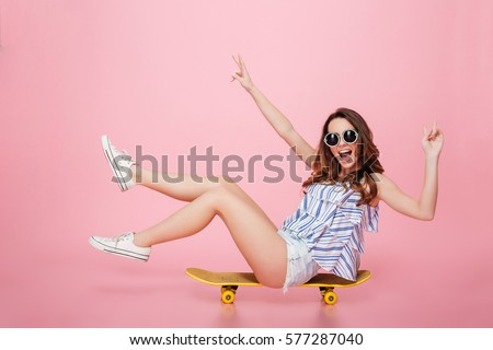 Cheerful young woman in sunglasses sitting on skateboard and having fun over pink background