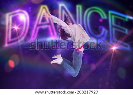 Cheerful young woman jumping against digitally generated colourful dance text
