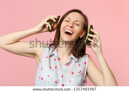 Cheerful young woman keeping eyes closed holding halfs of fresh ripe avocado fruit near ears isolated on pink pastel wall background. People vivid lifestyle relax vacation concept. Mock up copy space #1357481987