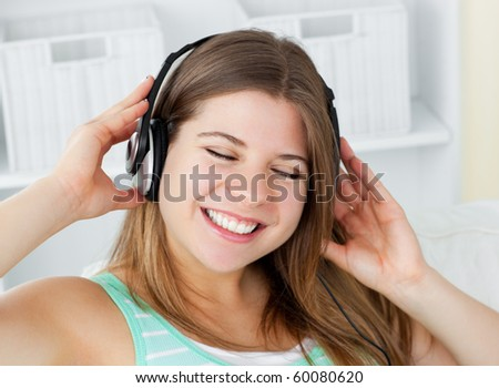 Cheerful young woman listening to music with headphones on a sofa at home