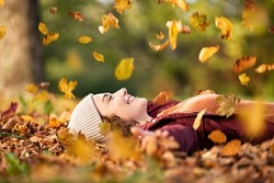Cheerful young woman lying over leaves with closed eyes and smiling. Woman lying over autumn ground relaxing at park. Casual joyful girl having fun throwing leaves in autumn park with copy space.