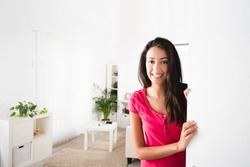 cheerful young woman opening her house front door and inviting friends at home