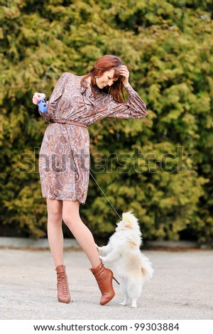 Cheerful young woman playing with her puppy