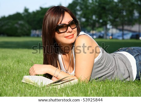 cheerful young woman reading book on the green grass
