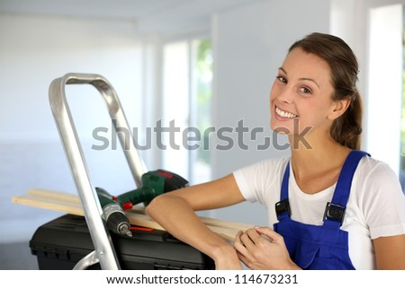 Cheerful young woman ready to reform house - stock photo