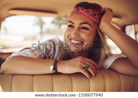 Cheerful young woman sitting in the car and looking away. Female wearing bandana relaxing in a old car and smiling.