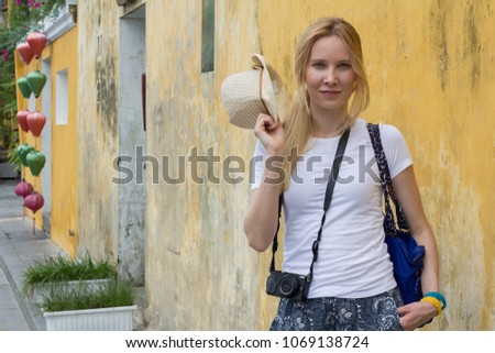 cheerful young woman tourist with camera on street #1069138724