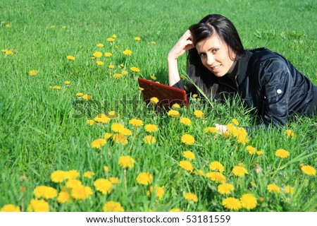 cheerful young woman using laptop on the green grass