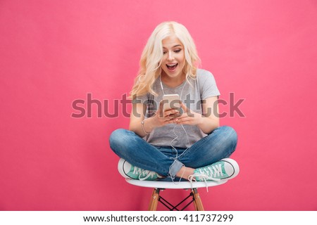 Cheerful young woman using smartphone with headphones over pink background
