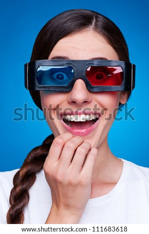cheerful young woman watching 3d film in stereo glasses over blue background