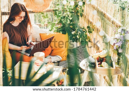 Cheerful young woman wearing brown blouse and sunglasses working on modern laptop sitting on the balcony with lemonade on sunny day.