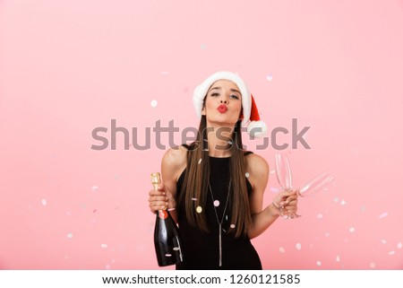 Cheerful young woman wearing Christmas hat celebrating standing isolated over pink background, holding bottle of champagne and glasses #1260121585