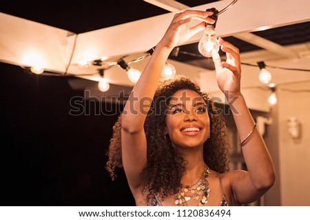 Cheerful young woman wearing party dress changing bulb light in patio. Happy smiling girl making preparation of party by adding lights outdoor. Happy beautiful woman enjoying fixing bulbs in backyard.