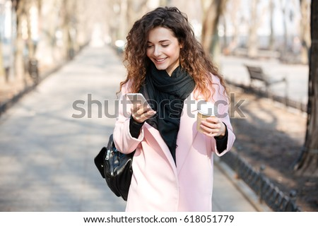 Cheerful young woman wearing pink coat using her phone in the sunny city street and drinking take away coffee in paper cup.