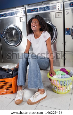 Cheerful young woman with clothes baskets sitting in laundry